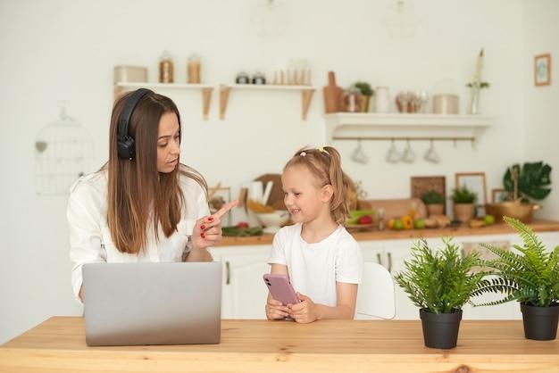 젊은 어머니는 집에서 일을 방해하는 딸을 꾸짖습니다. 격리. 원격으로 작업합니다.