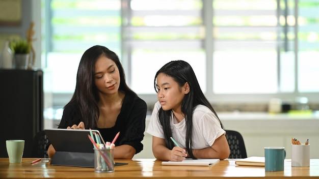 若い母親が座って、木製の学生の机で娘と一緒に宿題をしています。