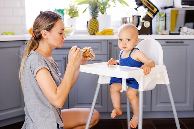 若い母親が台所の床に座って、白いハイチェアに座っている1歳の女の子にスプーンで餌をやる。