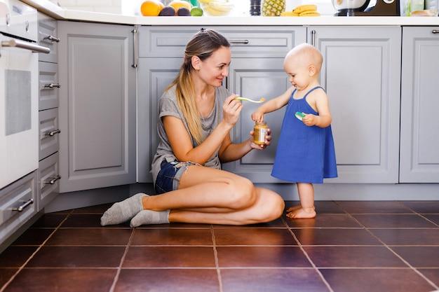 若い母親が台所の床に座って、1歳の娘にスプーンで餌をやる。