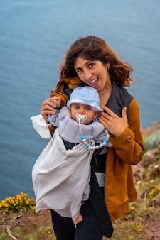 Молодая мать улыбается со своим младенцем на phare du cap frehel, морском маяке в кот-д'армор (франция). на вершине мыса фрехеля