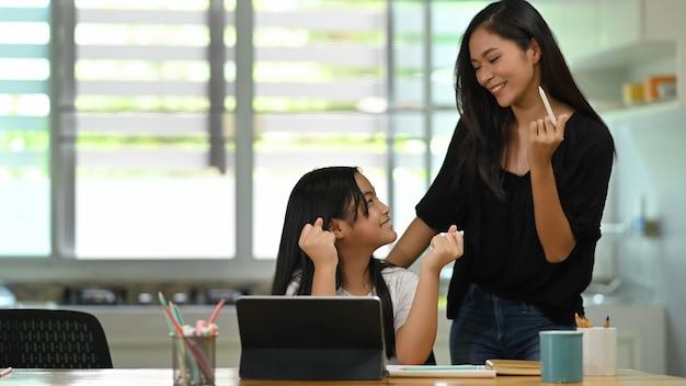Молодая мать стоит и обучение ее дочь на деревянный стол студент планшетный компьютер.