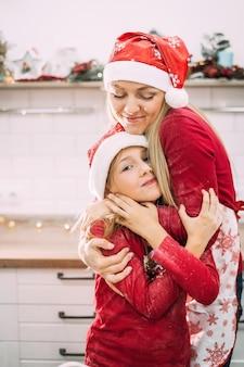 Молодая мать стоит со своим ребенком-подростком в красных свитерах на кухне, обнимаясь в шляпах санта-клауса