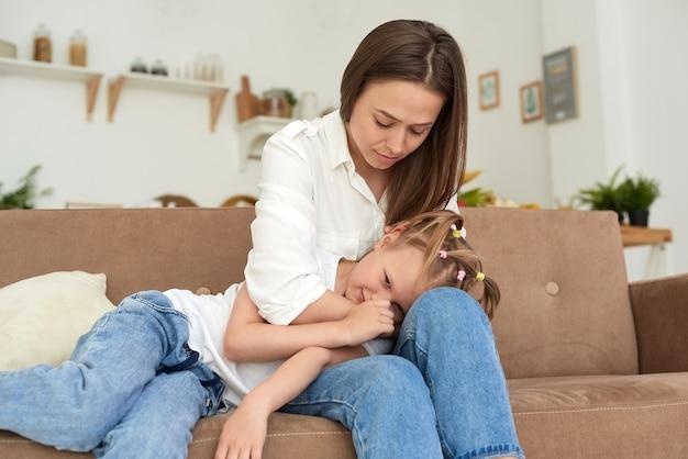Молодая мама поддерживает дочь, успокаивает ее и гладит по голове. маленькая девочка плачет