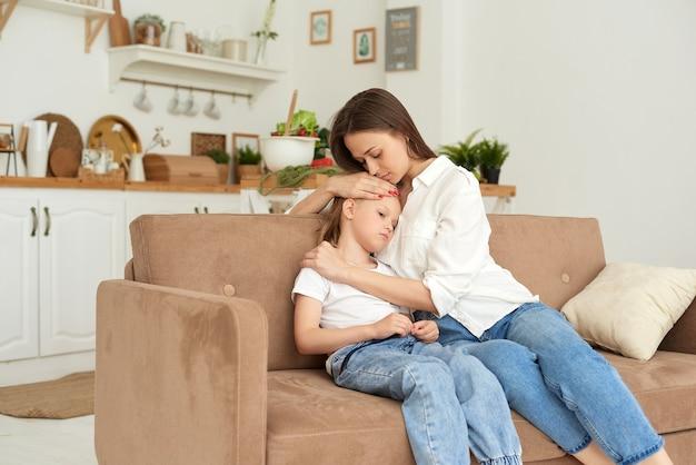 Молодая мама поддерживает дочь, успокаивает ее и гладит по голове.