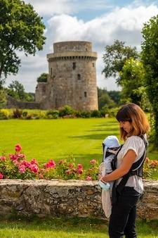 Молодая мама посещает шато де ла унаудай - средневековую крепость во французской бретани. исторический памятник франции