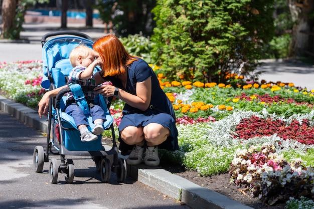 若い母親がベビーカーを持って歩き、1歳の息子が
