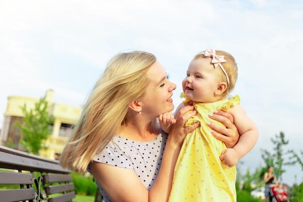 Молодая мама гуляет с малышом в парке летом, обнимает и целует, счастливое материнство