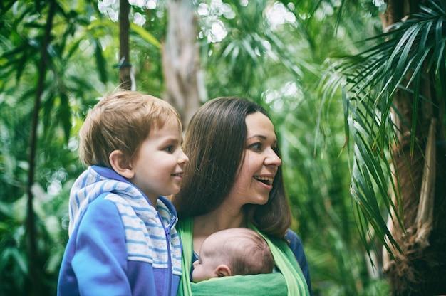 Молодая мама с ребенком в слинге и маленький мальчик гуляет в джунглях