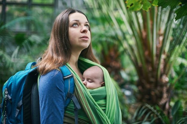 Молодая мама с ребенком в слинге гуляет в джунглях