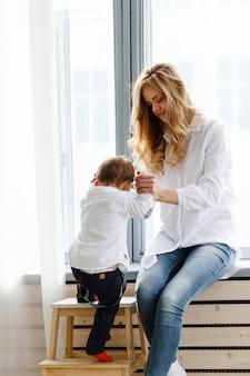 かわいい幼い息子を持つ若い母親は、窓の近くの明るく居心地の良いリビングルームで楽しんでいます