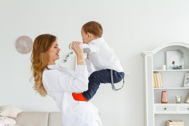 かわいい幼い息子を持つ若い母親が明るく居心地の良いリビングルームで楽しんでいます