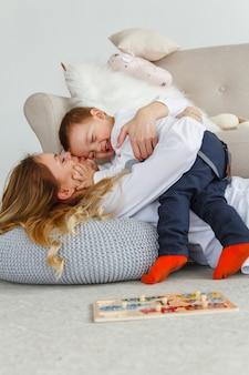 かわいい幼い息子を持つ若い母親は、明るく居心地の良いリビングルームの床に横たわって楽しんでいます