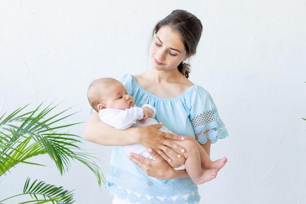 갓 태어난 아기를 안고 있는 한 젊은 엄마가 그것을 팔에 부드럽게 안고 집에서 껴안고 감탄하며 행복한 가족의 개념과 아이들의 탄생을 바라보고 있습니다.