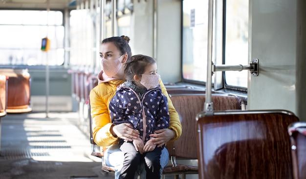 Молодая мама с маленьким ребенком в масках защищает себя от коронавируса в транспорте