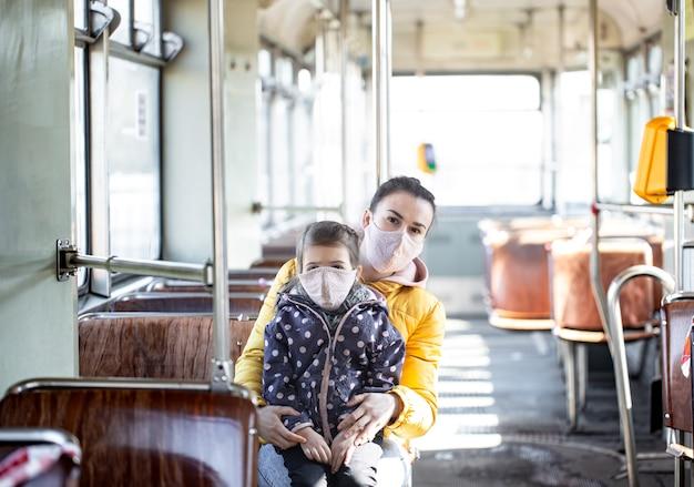 Молодая мама с маленьким ребенком в масках защищает себя от коронавируса в транспорте.