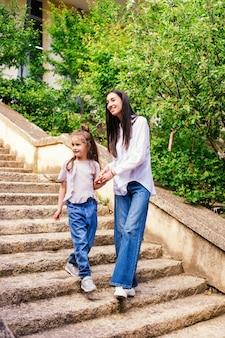小さな娘を持つ若い母親が階段を降ります。