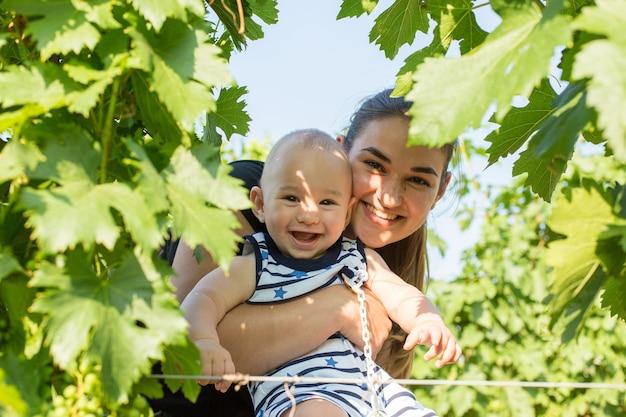 夏にブドウ園で幼児を持つ若い母親