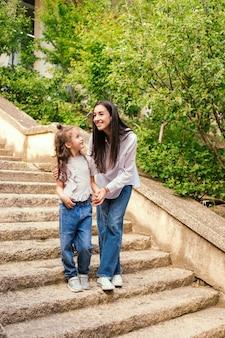 若い娘を持つ若い母親が階段を降りてきます。女性は女の子の手を握って話しかけます。