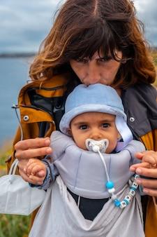 Молодая мать с младенцем в phare du cap frehel - морской маяк в кот-д'армор (франция). на вершине мыса фрехеля