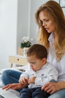 Молодая мама с любимым сыном в спальне на кровати с ноутбуком. работа дома с концепцией ребенка