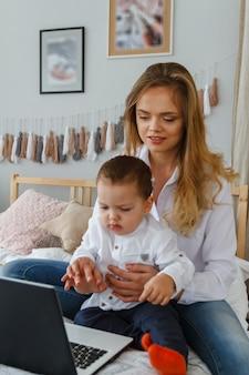 Молодая мама с любимым сыном в спальне на кровати с ноутбуком.