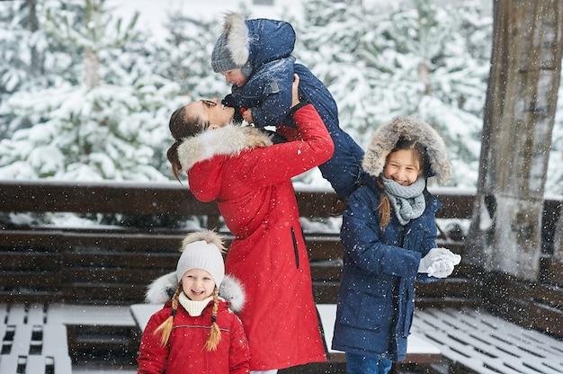 冬に楽しんでいる子供たちと若い母親