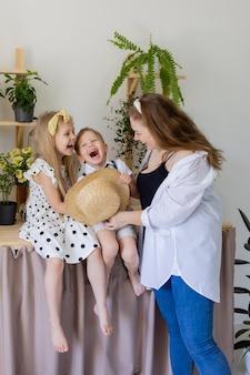 Молодая мама с сыном и дочерью смеется, обнимается и играет в помещении с домашними цветами