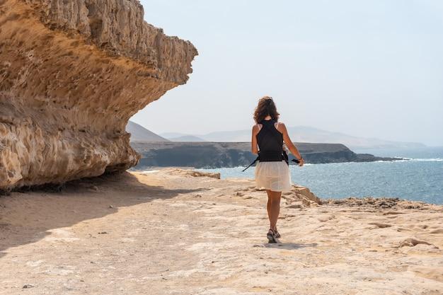 Молодая мать с сыном гуляют возле куэвас-де-ажуи, пахара, западное побережье острова фуэртевентура, канарские острова. испания