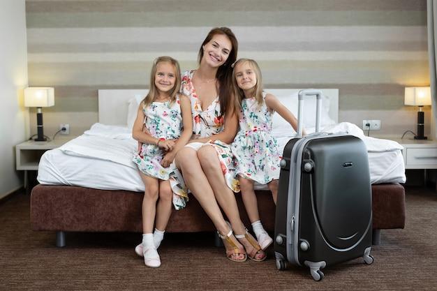 Молодая мама с дочерьми-близнецами сидит на кровати в отеле с чемоданом.