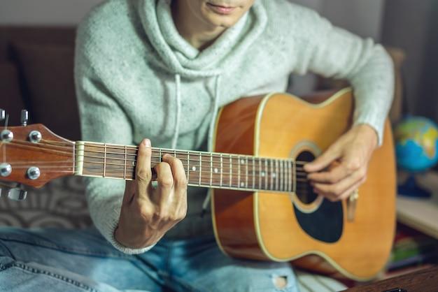 若いミュージシャンがアコースティックギターの演奏を学んでいます