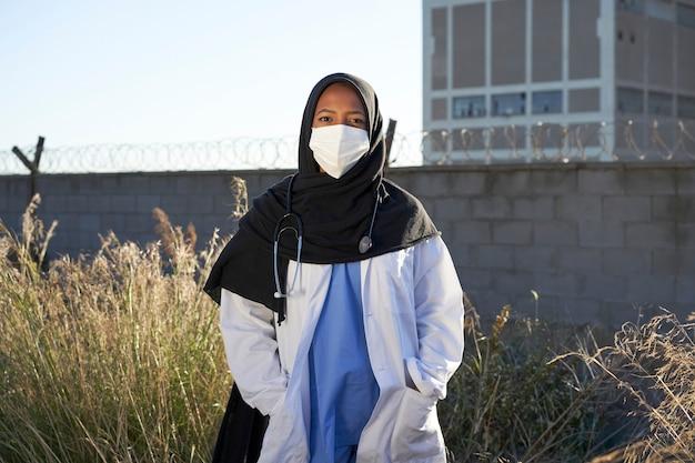 屋外でスカーフを持つ若いイスラム教徒の医師。ヒジャーブを持ったイスラムの医者がカメラに面した貧しい地域の外に立っています。ボランティアの医師。