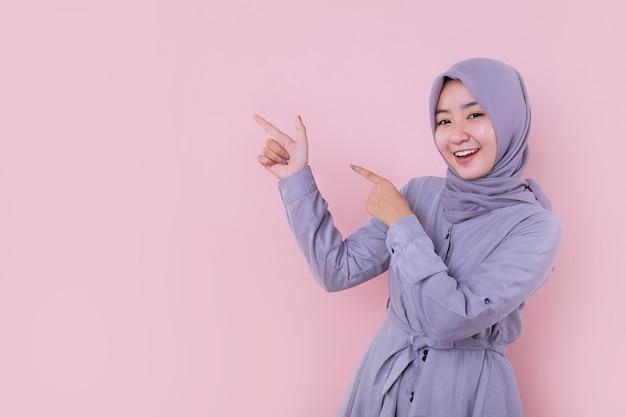 彼女の左側を指している若いイスラム教徒の少女
