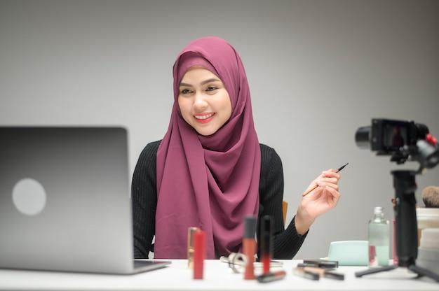 노트북을 사용하는 젊은 무슬림 여성 기업가는 온라인 및 뷰티 블로거 개념을 판매하는 흰색 배경 스튜디오를 통해 온라인 라이브 스트림 중에 화장품을 선물합니다.