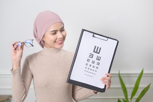 Молодая мусульманка держит тест на диаграмму зрения для измерения остроты зрения