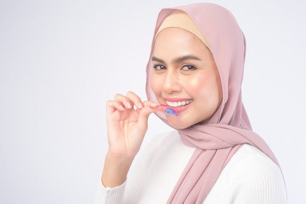 흰색, 치과 의료 및 교정 개념에 치아에 대 한 다채로운 보유자를 들고 젊은 무슬림 여성.