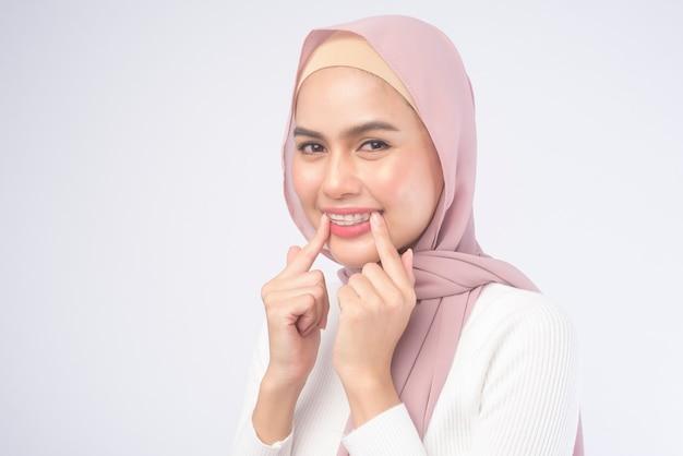 흰색 배경 스튜디오, 치과 의료 및 교정 개념 위에 치아를 위한 다채로운 리테이너를 들고 있는 젊은 이슬람 여성.