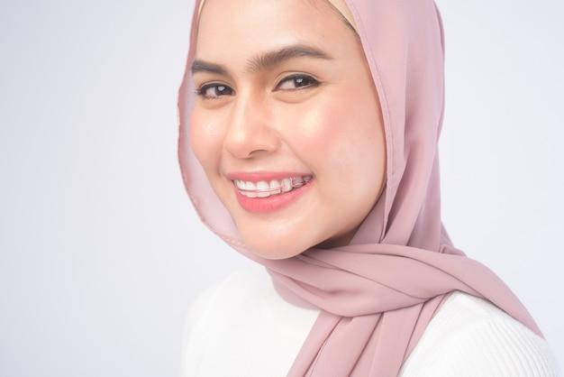 흰색 위에 치아를 위한 다채로운 리테이너를 들고 있는 젊은 이슬람 여성