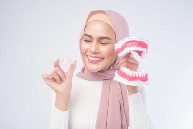 Invisalign 중괄호와 흰색, 치과 의료 및 교정 개념에 인간의 인공 치과 모델을 들고 젊은 무슬림 여성.