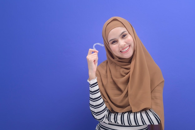 스튜디오, 치과 의료 및 교정 개념에서 인비절라인 교정기를 들고 있는 젊은 이슬람 여성. 프리미엄 사진