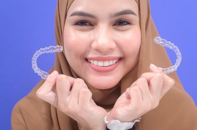 Молодая мусульманка, держащая брекеты invisalign в студии, стоматологическом здравоохранении и ортодонтической концепции.