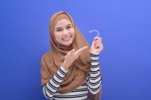 스튜디오, 치과 의료 및 교정 개념에서 인비절라인 교정기를 들고 있는 젊은 이슬람 여성.