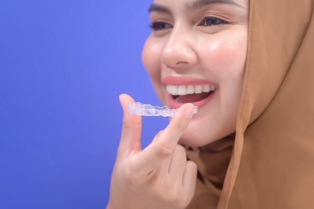 スタジオ、歯科医療、歯科矯正の概念でインビザラインブレースを保持している若いイスラム教徒の女性。
