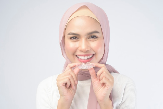흰색, 치과 의료 및 교정 개념에 invisalign 중괄호를 들고 젊은 무슬림 여성.