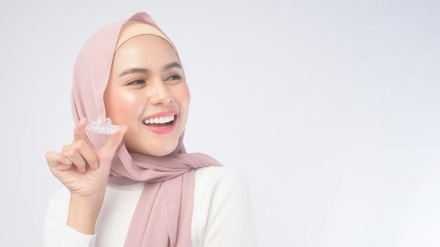 흰색 배경 스튜디오, 치과 의료 및 교정 개념 위에 인비절라인 교정기를 들고 있는 젊은 이슬람 여성.