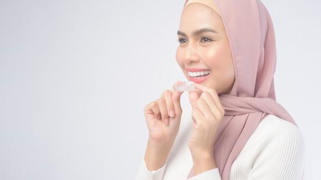 Молодая мусульманская женщина, держащая брекеты invisalign на белом фоне, студия, стоматологическое здравоохранение и ортодонтическая концепция.