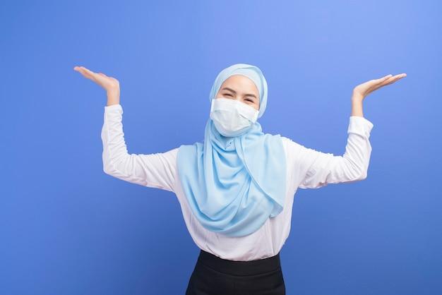 파란색 벽에 수술 마스크를 쓰고 hijab와 젊은 무슬림 여성.