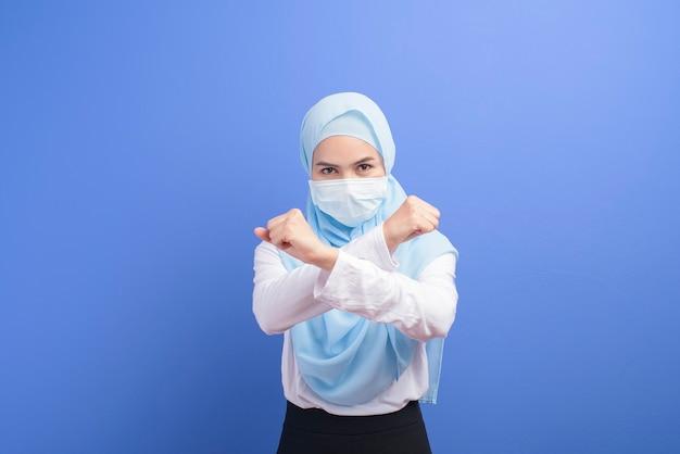 Молодая мусульманка в хиджабе в хирургической маске поверх синего