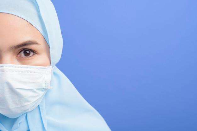 青の上にサージカルマスクを身に着けているヒジャーブを持つ若いイスラム教徒の女性