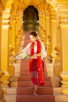 シュエダゴンパゴダと伝統的な居心地の良いジェスチャーでミャンマーの若い女性
